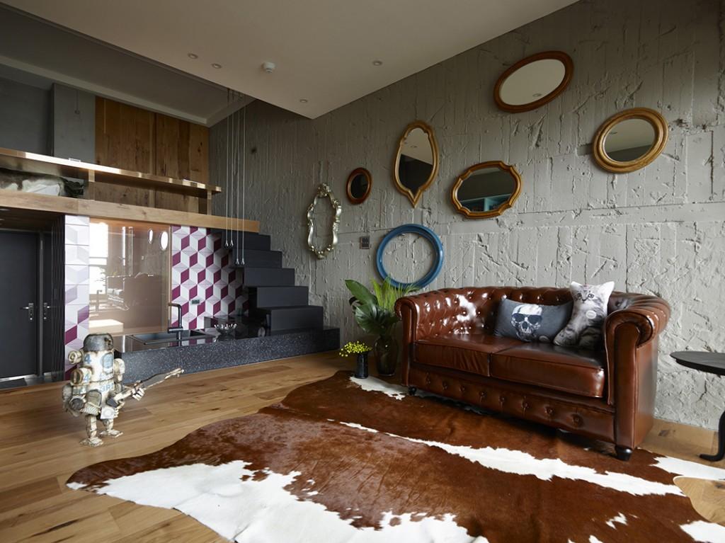 客廳牆身是粗獷水泥,牆上掛著各式各樣的鏡子作裝飾,形成一處像展覽般的場地。溫暖的木地台上鋪上一張牛皮地毯,和啡色的梳化達成色調上的一致。